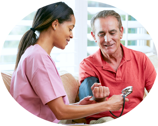 caregiver checking the blood pressure of elderly man