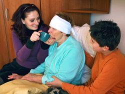 woman feeding an elderly woman in bed
