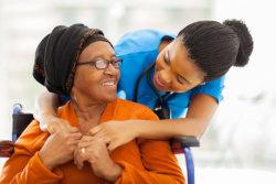 caregiver hugging an elderly woman