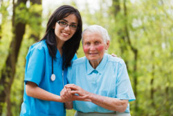 caregiver holding an elderly man outdoors