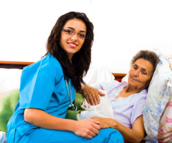 caregiver holding an elderly woman lying in bed