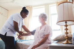 caregiver checking the blood pressure of an elderly woman