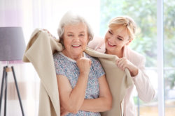 caregiver putting blanket over an elderly woman